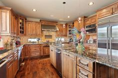 This kitchen features a butler's pantry, Jenn-Air stainless steel appliances, slab granite, duel dishwashers & staggered glazed cherry cabinetry.