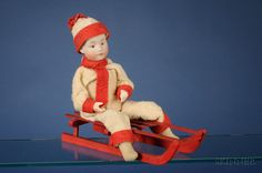 Heubach Bisque Boy on Sled Candy Container, with painted blue intaglio eyes, closed mouth, cylindrical carton body that opens at waist.