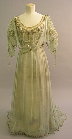 Description:  This evening dress made between 1908-1910 was worn by Maud Messel. It is made of silver gilt lame, covered with light green silk chiffon, embroidered with rosettes in pearls and glass. The dress has a long skirt with a train. The dress is worn with a green silk chiffon overdress, green silk chiffon scarves and silver braid. The design is aesthetic and medieval inspired. Its dramatic style indicates that it might have been worn as fancy dress. Front