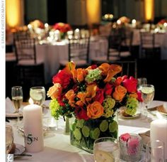 centerpieces of hot pink, orange, and green flowers set in square glass vases with slices of lime surrounding the flower stems in the water.