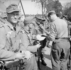 A British soldier checks the identity books of German soldiers at the Danish-German frontier post at Krusau (Danish Kruså), six kilometers north of Flensburg at the end of the war. Note the soldier at left holding his Soldbuch pay record. Irrespective of where they were located at the end of hostilities, German soldiers made concerted efforts to surrender to the Western Allies instead of the Russians.