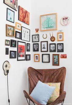 Parede galeria com quadros, fotos e objetos de afeto e poltrona butterfly de couro.