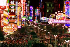 Shoppers crowd under colorful neon lights along Shanghai's bustling Nanjing Road.