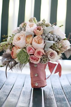 garden roses, succulents, lambs ear, feathers, and hypericum berries
