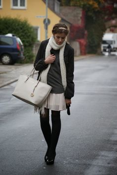 A charcoal coat and a nude pleated silk mini skirt are a great outfit formula to have in your arsenal. Shop this look for $189: http://lookastic.com/women/looks/scarf-belt-leg-warmers-tights-mini-skirt-tote-bag-turtleneck-coat/1949 — White Knit Scarf — Black Leather Belt — Black Leg Warmers — Black Tights — Beige Pleated Silk Mini Skirt — Grey Leather Tote Bag — Charcoal Turtleneck — Charcoal Coat