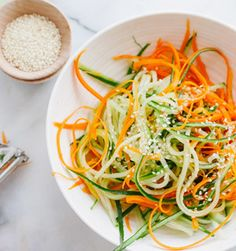 Asian Cucumber & Carrot Slaw 1 large English cucumber 2 medium carrots, peeled 2 tablespoons rice vinegar 1 tablespoon cider vinegar 1 teaspoon water 1/2 teaspoon sugar 1/2 teaspoon sesame oil 1 tablespoon sesame seeds 1/4 cup chopped cilantro Using a julienne peeler or grater, shred the cucumber and carrots into long strips. Toss the vegetables in a medium bowl, along with the vinegars, water, sugar, and sesame oil. Garnish with sesame seeds and cilantro. Chill until ready to serve