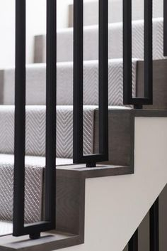 Chic staircase is fitted with modern iron spindles and covered in a gray herringbone stair runner. Chic staircase is fitted with modern iron spindles and covered in a gray herringbone stair runner.