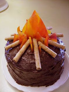 "LDS Young Women: Camp Fire Cake:  Triple fudge cake mix, Caramel filling, Fudge ganache frosting, Pirouette cookies ""sticks"", & melted butterscotch and cinnamon hard candies ""flames""."