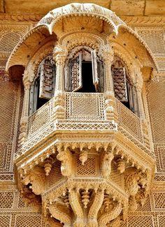 [Ventana en arco saliente bellamente tallada en piedra arenisca amarilla con impresionante trabajo de incrustación; Jaisalmer, Rajasthan, India]