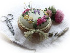 This elegant and simple silk ribbon pin cushion is suitable for a beginner to attempt. Design measures 3 inches or in diameter.