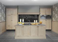 Koken zoals in grootmoeders tijd, maar met de allernieuwste materialen en technieken: eiken deuren en een eiken lambrisering met een verouderde, geceruseerde look, een werkblad in Belgische blauwe steen waarvan de randen zijn afgewerkt met 'geciseleerde' lijntjes,  en zwarte tegeltjes ('zelliges') tegen de muur achter het extra brede kookgedeelte.  Het afwaseiland heeft Les Flandres-plinten. De royale side-by-sidekoelkast en -vriezer zitten ingewerkt in de kasten.