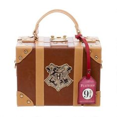 Are you ready to board the Hogwarts Express at Platform 9 3/4? This Hogwarts trunk inspired handbag features the Hogwarts crest and snap closure. Perfect for wands, potions, and everyday essentials.