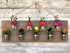 Baby food jars fixed to a board for a cute flower presentation. Adorable!!