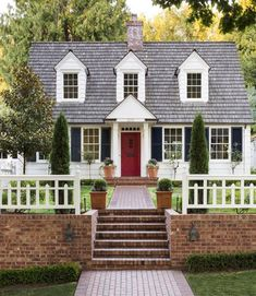 This Seattle home has for days thanks to its red door and black shutters. Dutch Colonial Exterior, Café Exterior, Cape Cod Exterior, Colonial House Exteriors, Dream House Exterior, Exterior House Colors, Colonial Cottage, Colonial Style House, Dutch Colonial Homes