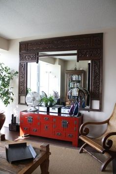 red oriental console table looks cool with an Indian frame mirror