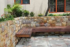 Floating wooden bench on a stone mason wall that is a raised planter.