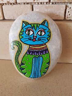 Cat pattern design painted on a smooth oval river stone!  The pebble was found by me in the River Jordan in Israel.  The stone is a beautiful piace of art that can be used as a decoration on your desk, shelf, meditation room, paperweight, door stopper and etc.  Its colorful and interesting, very well suited in the House, in the apartment or on the balcony.  every stone is one of a kind. Its painted with fine art quality acrylic colors and protected with 2 or 3 layers of high quality acrylic…