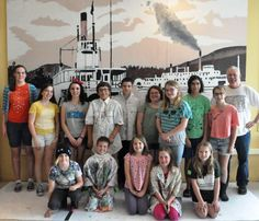 Penticton Art Gallery Young at Art group in front of a newly painted mural for the SS Sicamous. The mural is based on a photo of the SS Aberdeen (the first steam ship on Okanagan Lake!).