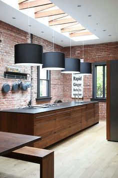 Simple kitchen for small space easily reproduce inexpensively; hanging lights with shade, brick wall, simple wall rack for pans. Love the brownstone and natural light. Looks less heavy