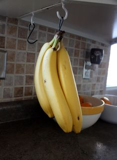 Screw a hook into the underside of your kitchen cabinets or a shelf in your pantry. Use an S hook to hang your bananas and keep them off the counter.