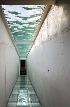 Skylight over glass bridge with water above
