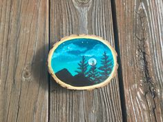 This is an acrylic painting of a beautiful mountain silhouette. The locust wood this painting is created on gives the final piece a textured and rustic finish. This adds something special to the subject matter focusing on nature and the mountains. The background of this painting is made up of vivid teal and blue.  SIZE OF WOOD: Approximately 5 x 4.25 and 1.25 thick  Each side of the wood is sealed with two layers shellac before the painting is created to ensure the wood is protected. Each…