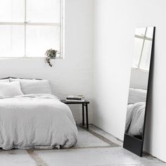 Minimal bedroom with simple mirror leaning against wall