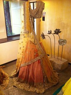 Colourful orange and yellow Sabyasachi lehenga with blouse and dupatta. Indian fashion.