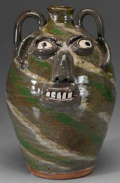 "B.B. Craig stoneware pottery face jug, (Burlon Craig, Catawba County, North Carolina, 1914 to 2002), swirled body with green and ivory diagonal bands, broken-china teeth, stamped on base ""BB Craig, Vale NC""."