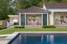 An in-ground swimming pool framed with grass is positioned in front of a beautifully appointed pool house boasting decorative hunter green barn doors that flank a doorway.