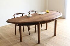 The Legere Bean Dining Table is made of walnut in the shape of a bean (or a slightly askew half moon). Below the tabletop, a second layer of walnut is used for dining room storage.
