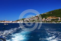 Photo about Boat trail on blue sea water near shore with buildings and forest. Image of mountain, ocean, traveling - 92517314 Trail, Buildings, Waves, Ocean, Boat, Celestial, Stock Photos, Outdoor, Image