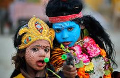 Indian children dressed as Hindu God Shiva, right, and Parvati, hold a toy gun as they pose for a photograph during the annual traditional fair of Magh Mela at the confluence of the rivers Ganges, Yamuna and the mythical Saraswati, in Allahabad, India, on January 15, 2012. (AP Photo/Rajesh Kumar Singh)