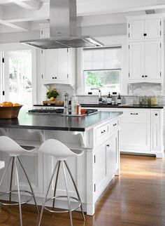 Gourmet kitchen features a stainless steel vent hood suspended over a white center island adorned with oil rubbed bronze hardware topped with contrasting soapstone fitted with a gas cooktop lined with Onda Barstools.