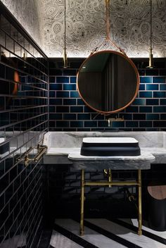 Dramatic bathroom cloakroom with a mix of classic brass detailing, a 1950s copper mirror, contemporary lighting. A bold approach to color and pattern using dark blue subway tiles. Bathroom by House of Beast | Photo by Dennis Lo