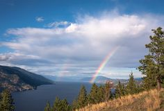 A dissipating storm system with Rainbows over Okanagan Lake, Kelowna, British Columbia, Canada. Waterfront Property For Sale, Canadian Things, Cloud Photos, O Canada, Vernon, British Columbia, Rainbows, Lakes, Photo Galleries