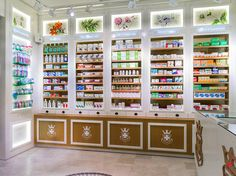 PALAU pharmacy by MARKETING JAZZ Barcelona Spain the art nouveau lamps, the layered lighting used to illuminate the products on display, then the labelling in English, graphic illustrations featuring plants and photographs of women, to the characteristic smells and fragrances associated with each of the three rooms: medicines, nature products and cosmetics.