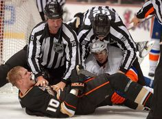 Anaheim Ducks right wing Corey Perry, lower left, yells at the referee after fighting with New York Islanders defenseman Travis Hamonic