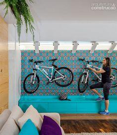 Nesta sala, a bicicleta fica guardada em lugar de destaque - pendurada em um painel. A cobertura de vidro com estrutura metálica era original do jardim de inverno. Assumida no ambiente, trouxe mais luz natural. Com marcenaria da loja 1/4 de Gente, o móvel azul funciona como degrau na hora de manusear a bicicleta. Os suportes e o adesivo são do mesmo fornecedor. Sobre o sofá, almofadas da Codex Home.