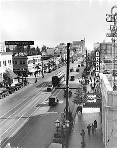 Hollywood Boulevard, looking east from McCadden Place in 1928. We can see the vertical sign for Grauman's Egyptian Theater, with the Pig 'n' Whistle restaurant next door—both are still here. Across the street is a sign for the Myer Siegel & Co. department store. Note the car strangely in front of the streetcar.