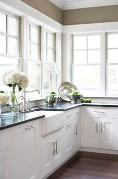 I love all of the windows and the Belfast sink!  I love being able to look outside while washing dishes...It makes it a little less horrible. ✤ nice corner kitchen with a wall of windows, granite tops, shaker style cabinets