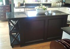 """Our new custom island....we just applied molding to create the look of panels, added a 12"""" bookshelf on the end, painted black and added granite.  Great DIY project....love it!"""