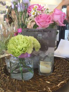 Colorato #centrotavola, composto da semplici vasetti con fiori e disco di legno come base per la foto col nome del tavolo!