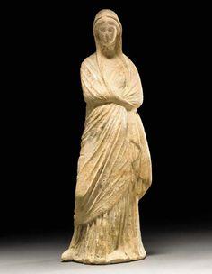 A GREEK TERRACOTTA FEMALE FIGURE Hellenistic Period, Circa 3rd Century B.C.