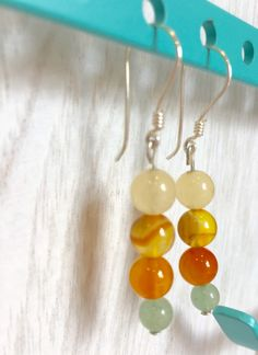 Autumn Kiss A harmonious combination of warm colors, a soft orange, yellow, and light green.  Materials: - Orange Sardonyx - Jade - Green Chalcedony - Pure silver .95 Dimensions: 2 1/16 in long