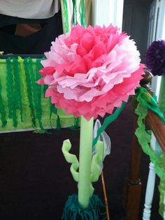 Tissue paper flowers top the pool noodle which cover wooden dowel   Concrete base covered with grass skirt.