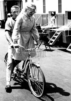 Paul Newman and Joanne Woodward riding around a movie set, 1970