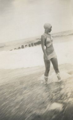 Woman wearing one-piece bathing suit and swim cap enjoying the surf 1930s
