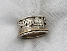 Sterling silver gold spinner ring. by MayaOr. Very steampunk. If only the flower pedals were diamonds.
