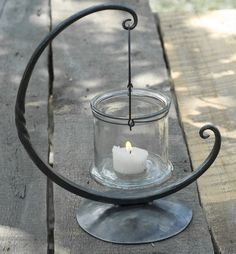 Form and beauty follow function with this rustic and elegant Moon Lantern.  Enjoy the warm glow of the elevated candlelight, at your dining table, end table, or bedside. Inspired by the full moon in the night sky here in Vermont. This hand forged piece will warm and inspire your home with a subtle grace and beauty that is evocative of the lunar night. The wall mount option is a great border around focal points of your home or apartment, such as entry ways, ding room walls, outside your front…